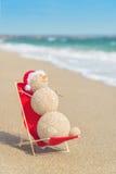Muñeco de nieve de Sandy en el sombrero de santa que toma el sol en salón de la playa Imagen de archivo