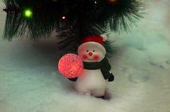 Muñeco de nieve debajo del árbol de navidad imagen de archivo