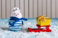 Muñeco de nieve decorativo hecho a mano con el trineo rojo y Imagenes de archivo