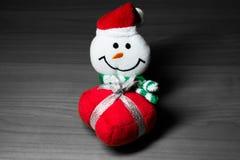 Muñeco de nieve decorativo que sonríe en un fondo blanco y negro Imagen de archivo