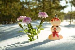 Muñeco de nieve del invierno cerca de la flor de la nieve Foto de archivo