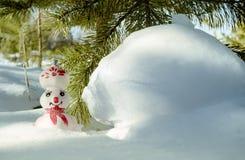 Muñeco de nieve del invierno cerca de la nieve acumulada por la ventisca Foto de archivo