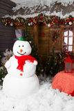 Muñeco de nieve del invierno rodeado por las decoraciones de la Navidad Fotografía de archivo libre de regalías