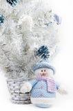 Muñeco de nieve del juguete al lado de un árbol de navidad blanco Foto de archivo