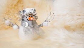 Muñeco de nieve del juguete de la Navidad (Año Nuevo) en fondo de la piel de las ovejas blancas Imagenes de archivo