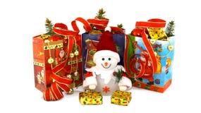 Muñeco de nieve del juguete de la Navidad en el medio de los paquetes del regalo Imagen de archivo