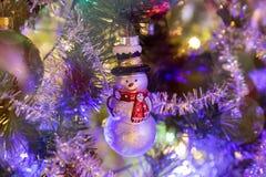 Muñeco de nieve del juguete en el árbol de navidad foto de archivo
