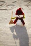 Muñeco de nieve del juguete en la arena Imágenes de archivo libres de regalías