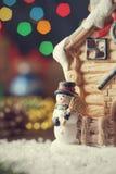 Muñeco de nieve del juguete de Navidad cerca de la casa miniatura en fondo del bokeh Fotos de archivo libres de regalías