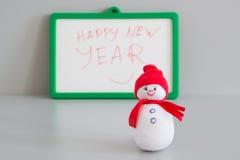 Muñeco de nieve del juguete y saludo de Feliz Año Nuevo fotografía de archivo