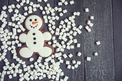 Muñeco de nieve del pan de jengibre con la melcocha que pone en fondo de madera gris La Navidad o composición del Año Nuevo Tarje Imagenes de archivo