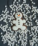 Muñeco de nieve del pan de jengibre con la melcocha que pone en fondo de madera gris La Navidad o composición del Año Nuevo Tarje Fotografía de archivo