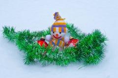Muñeco de nieve del ` s del Año Nuevo con los juguetes en la nieve Foto de archivo libre de regalías