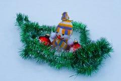 Muñeco de nieve del ` s del Año Nuevo con los juguetes en la nieve Fotos de archivo