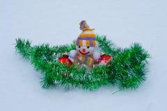 Muñeco de nieve del ` s del Año Nuevo con los juguetes en la nieve Foto de archivo