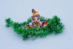 Muñeco de nieve del ` s del Año Nuevo con los juguetes en la nieve Imagenes de archivo