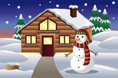 Muñeco de nieve delante de una casa Imagen de archivo libre de regalías