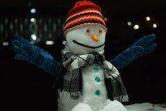 Muñeco de nieve muñeco de nieve divertido en un fondo oscuro de la noche, con las luces intrépidas en el fondo Año Nuevo 2019 fotos de archivo