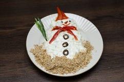 Muñeco de nieve divertido hecho del souce blanco en placa Foto de archivo libre de regalías