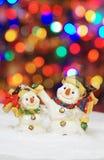 Muñeco de nieve dos con las luces de la Navidad en el fondo Foto de archivo libre de regalías