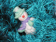 Muñeco de nieve en el oropel azul Foto de archivo libre de regalías