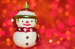 Muñeco de nieve en fondo rojo del bokeh Imagen de archivo libre de regalías
