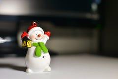 Muñeco de nieve en la mesa delante del ordenador Imagen de archivo libre de regalías