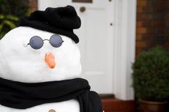 Muñeco de nieve en la puerta principal imagenes de archivo