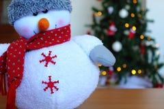 Muñeco de nieve en nieve sobre el árbol de navidad borroso en fondo del bokeh de la luz del brillo fotos de archivo libres de regalías