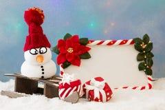 Muñeco de nieve en un trineo Fotos de archivo libres de regalías