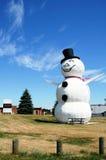 Muñeco de nieve enorme contra un cielo azul imagenes de archivo