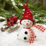 Muñeco de nieve feliz con el trineo de madera Imágenes de archivo libres de regalías