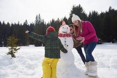 Muñeco de nieve feliz de la fundación de una familia Fotos de archivo