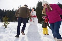 Muñeco de nieve feliz de la fundación de una familia Foto de archivo libre de regalías