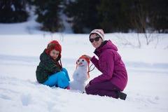 Muñeco de nieve feliz de la fundación de una familia Imagen de archivo libre de regalías