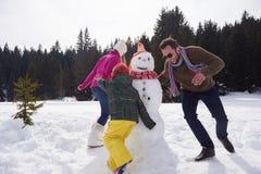 Muñeco de nieve feliz de la fundación de una familia Imagenes de archivo