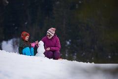 Muñeco de nieve feliz de la fundación de una familia Imágenes de archivo libres de regalías