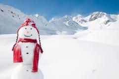 Muñeco de nieve feliz en montañas Imagenes de archivo