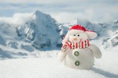 Muñeco de nieve feliz en montañas Fotos de archivo