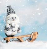 Muñeco de nieve feliz en un trineo Imágenes de archivo libres de regalías