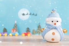 Muñeco de nieve feliz que se coloca en fondo azul de la nieve de la Navidad del invierno Feliz Navidad y tarjeta de felicitación  Foto de archivo libre de regalías