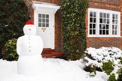 Muñeco de nieve fuera de la casa Imagenes de archivo