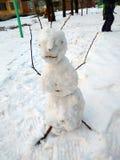 Muñeco de nieve grande, asustadizo en un patio de la ciudad fotografía de archivo