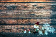 Muñeco de nieve grande y pequeño en un casquillo rojo en la tabla de madera fotografía de archivo