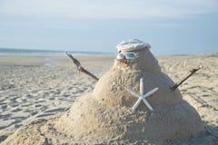 Muñeco de nieve hecho fuera de la arena con el sombrero Fotos de archivo libres de regalías