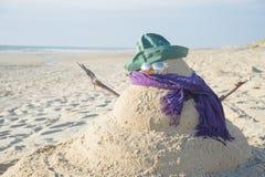 Muñeco de nieve hecho fuera de la arena con el sombrero Imagen de archivo