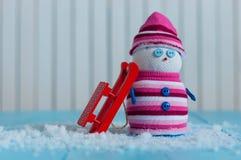 Muñeco de nieve hecho a mano en suéter del color del marsala con rojo Imagen de archivo libre de regalías
