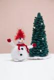 Muñeco de nieve hecho punto con el árbol de navidad imagen de archivo libre de regalías