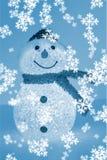 Muñeco de nieve iluminado con los copos de nieve blancos en fondo azul Fotos de archivo