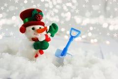 Muñeco de nieve lindo acurrucado en nieve con la pala Fotografía de archivo